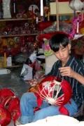 Мальчик мастерит китайские фонарики. Хойан