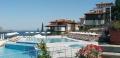 Бассейн, корпуса отеля, шезлонги и зонтики на фоне Черного моря