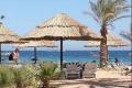 Туристы отдыхают под соломенными зонтами на побережье Красного моря в Шарм-эль-Шейхе