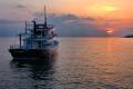 Корабль в лучах заката в прибрежных водах Лутраки