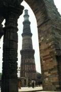 Вид на кирпичный минарет Кутб-Минар в Дели из-под свода арки