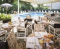 Столики в летнем кафе рядом с бассейном в Милано Мариттима
