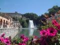 Вид сквозь розовые настурции на водопад, канал и набережную в коммуне Фьюджи