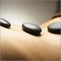 Черные камни на спине человека. Спа-процедуры в коммуне Фьюджи